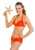 b1cf0575fc5a ... Retrato de mujer joven sonriente en traje de baño estrella de mar ...