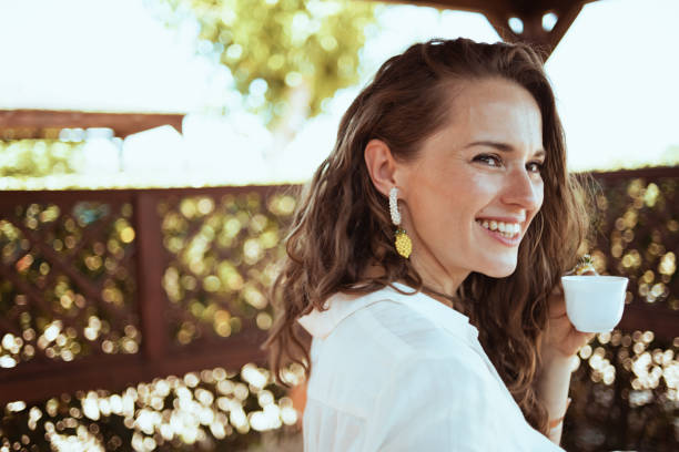 Portrait of smiling young woman in white shirt stock photo