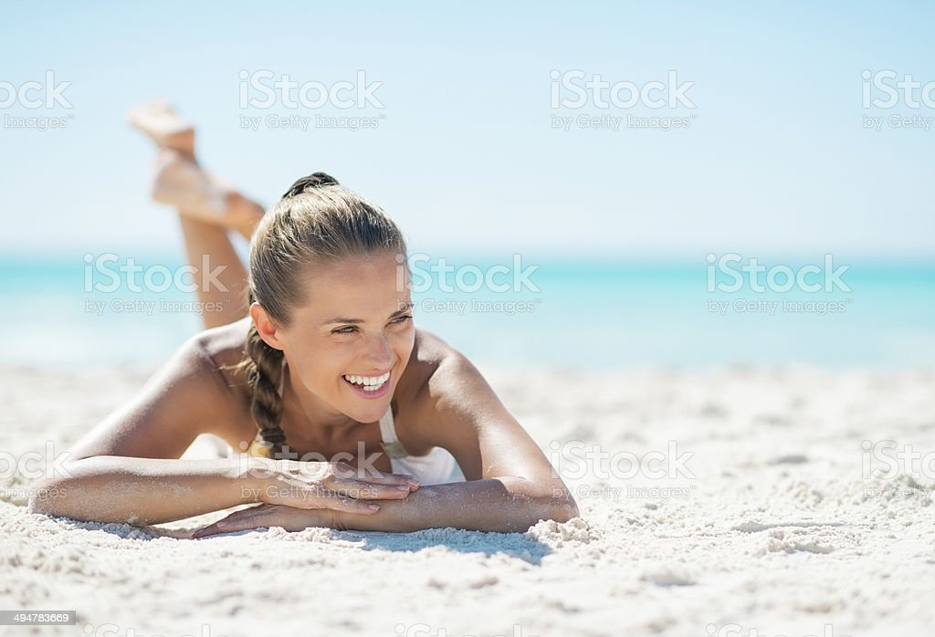 Portrait of smiling young woman laying on beach stock photo