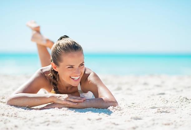 ritratto di sorridente giovane donna posa sulla spiaggia - abbronzarsi foto e immagini stock