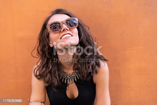 Portrait of smiling young woman with sunglasses looking up, on street.