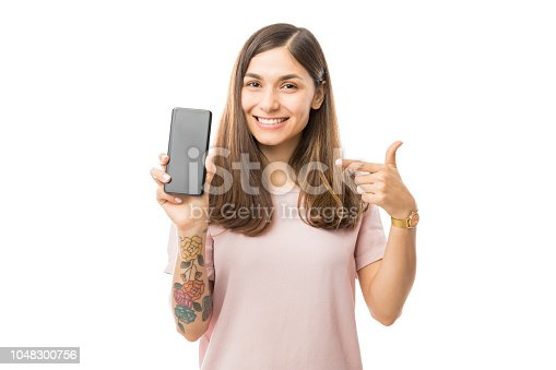 istock Portrait Of Smiling Young Woman Pointing At New Smartphone 1048300756