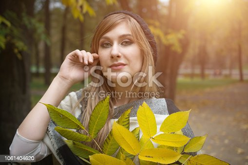 istock Portrait of smiling young woman with autumn leafs 1061404620