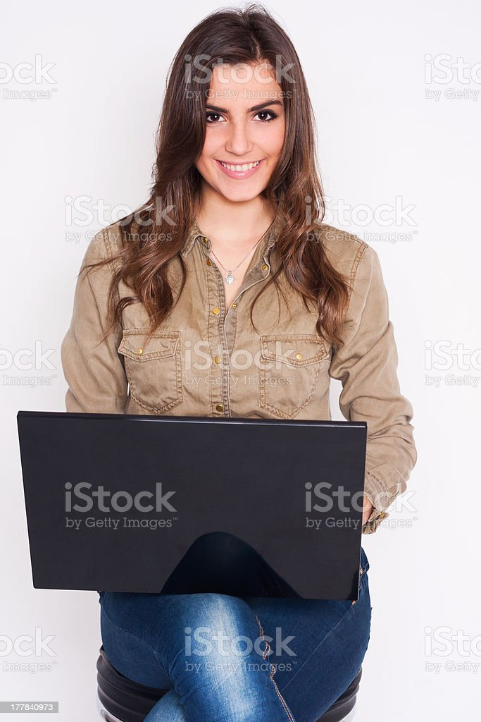 Portrait of smiling young woman working on a laptop royalty-free stock photo
