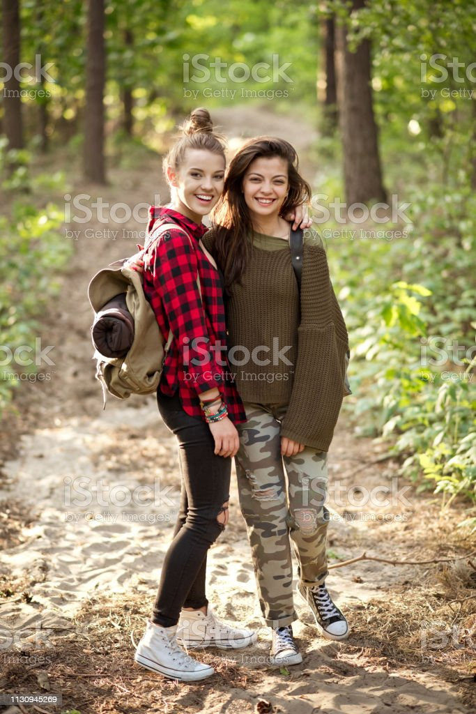 Portrait of smiling young women standing in forest Portrait of smiling beautiful young hikers standing on footpath. Happy female hipster is exploring with friend. They are spending weekend in forest. 20-24 Years Stock Photo