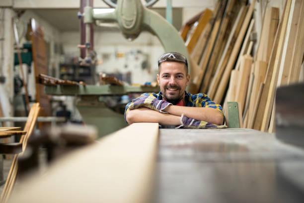 porträt von lächelnden jungen schreiner stehen neben einer maschine und werkstoff holz in seiner tischlerwerkstatt. - schreiner stock-fotos und bilder