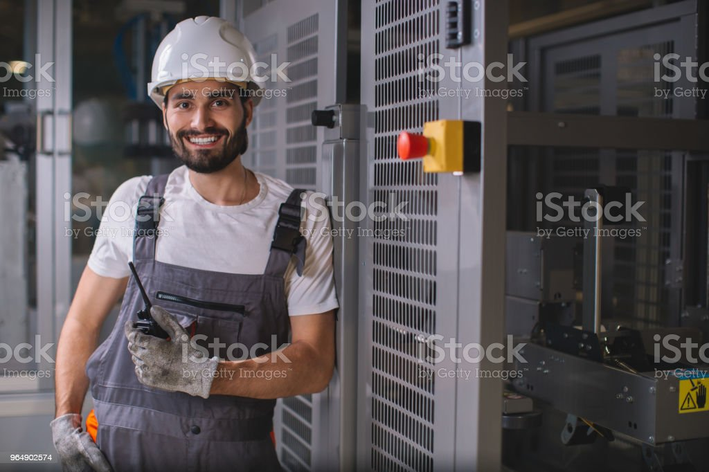 夜班上的微笑年輕工人肖像 - 免版稅一個人圖庫照片