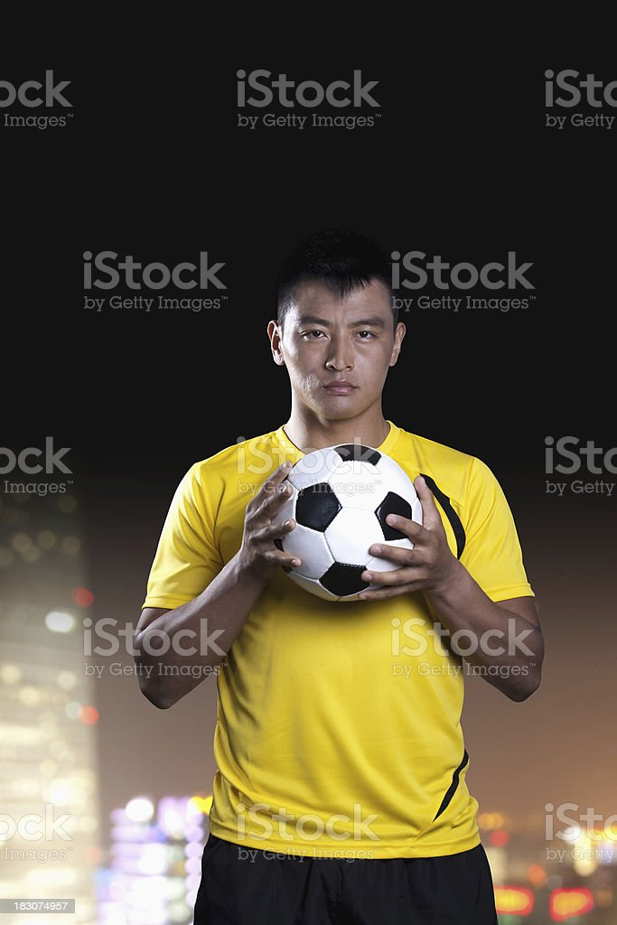 Portrait of soccer player holding a ball, background at night royalty-free stock photo