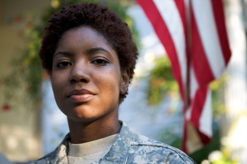 Portrait of a African American Soldier in Uniform with flag in background.