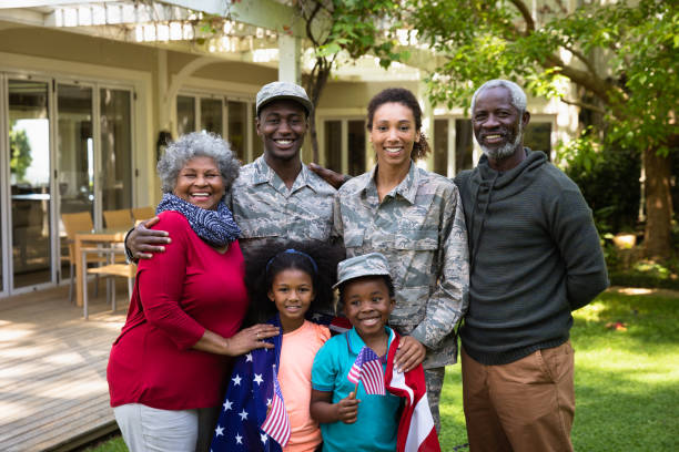 Portrait of soldier with family Portrait of a young adult African American male soldier and a young adult mixed race female soldier with thier diverse multi-generation family in the garden outside their home, embracing and smiling to camera, a US flag draped over the shoulders of the kids military stock pictures, royalty-free photos & images