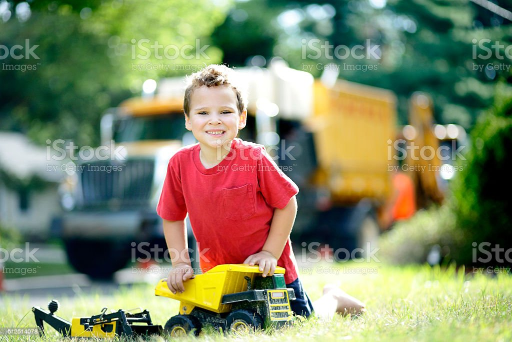 Portrait of special needs boy playing with his toy trucks stock photo