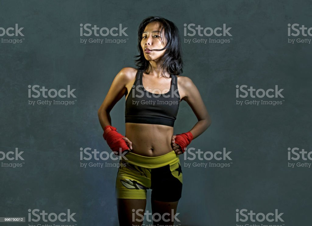 portrait of sporty and fit fighter Asian Chinese woman using wrist wraps training mma fight sport or boxing workout looking dangerous in badass pose isolated on dark grunge background stock photo