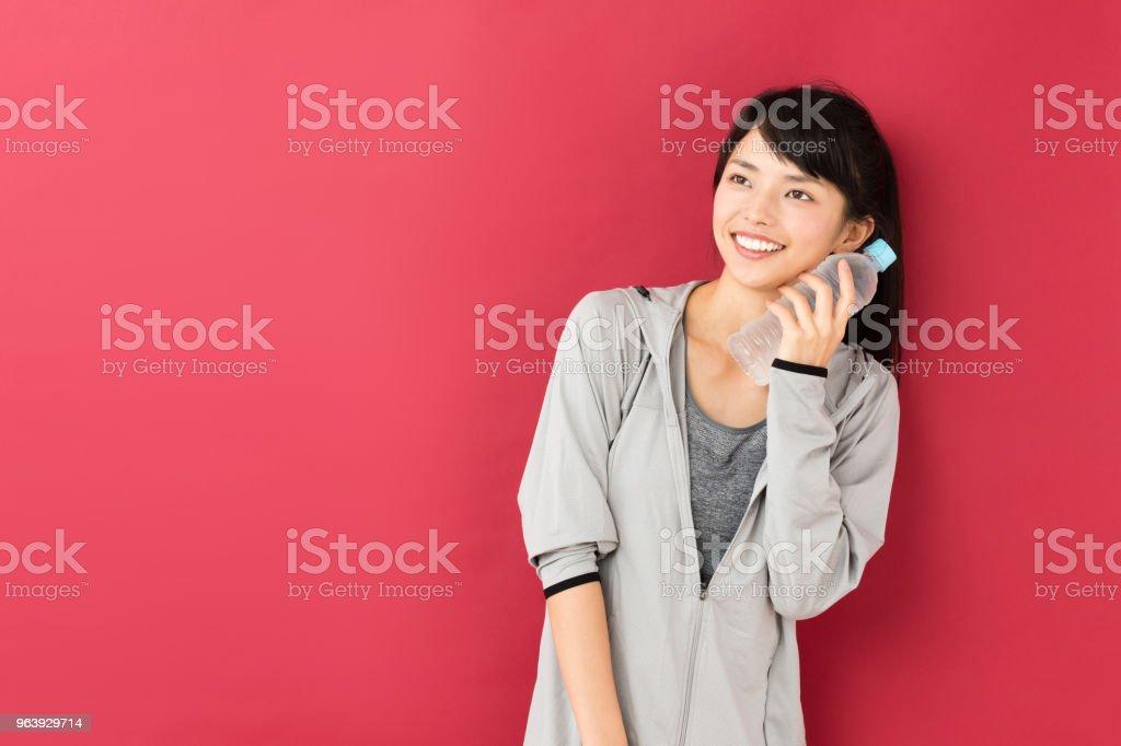 赤の背景に分離されたスポーティなアジアの女性の肖像画 - 1人のロイヤリティフリーストックフォト