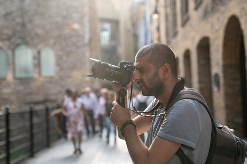 Portraits of adult photographer photographing streets of city of London. Architectural style of city is seen on the background.  He is in casual clothings and has short hair. Selective focus on model while large group of people are seen blurred. Shot under daylight with a full frame mirrorless digital camera.