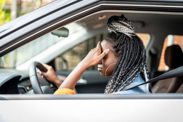 porträt von gestressten afrikanische frau im auto - migräne vorbeugen stock-fotos und bilder