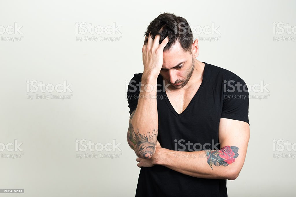 Portrait of stressed man with tattoos stock photo