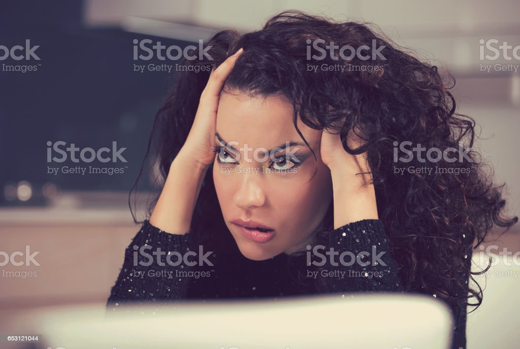 Portrait of stressed sad young housewife sitting in modern kitchen stock photo