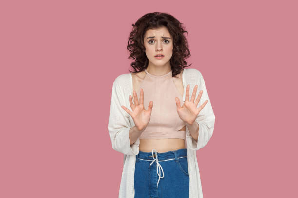 Portrait of stressed scared beautiful brunette young woman with curly hairstyle in casual style standing and looking at camera with panic and stop sign. Portrait of stressed scared beautiful brunette young woman with curly hairstyle in casual style standing and looking at camera with panic and stop sign. indoor studio shot isolated on pink background. nerd hairstyles for girls stock pictures, royalty-free photos & images