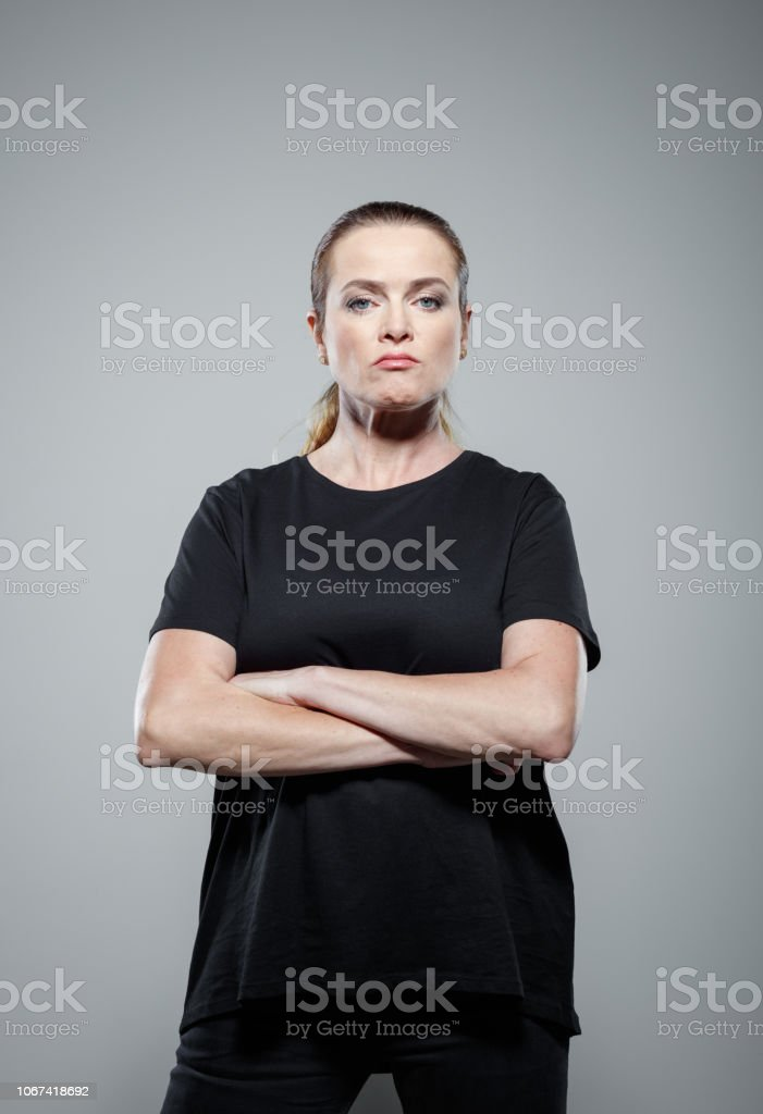 Portrait of strong and confident woman Powerful woman wearing black clothes, standing with arms crossed against grey background, staring at camera. Studio shot. 35-39 Years Stock Photo