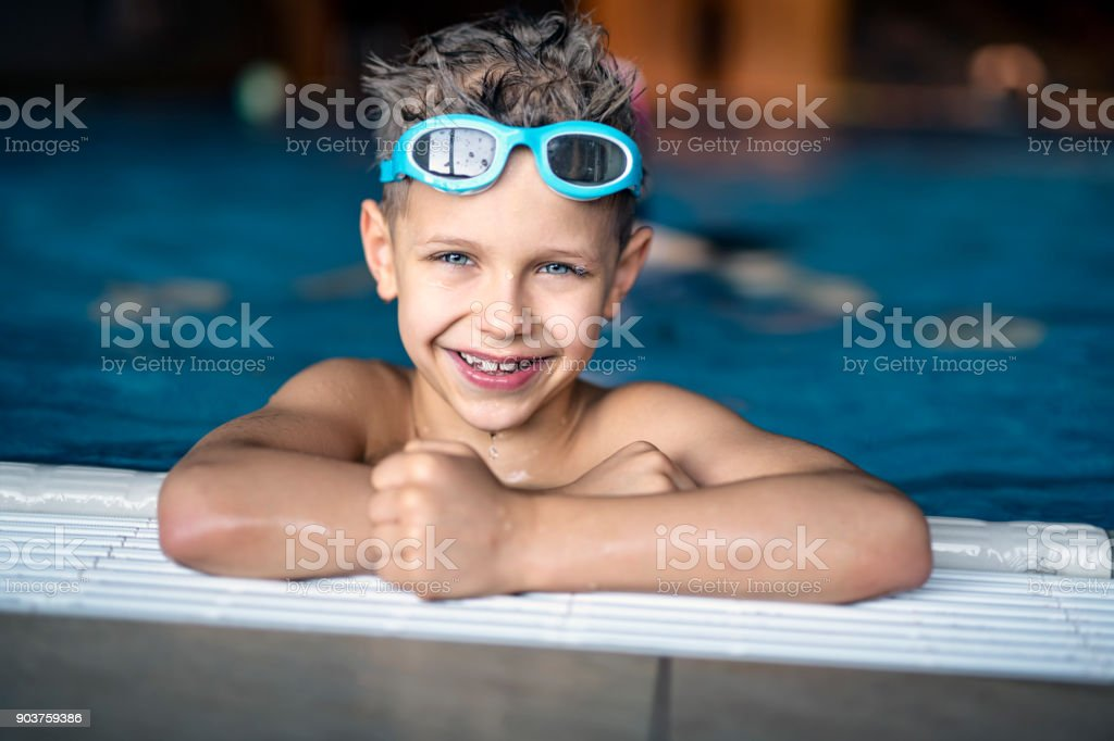 Portrait of strong little boy at the swimming pool stock photo