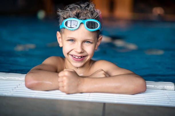 Portrait of strong little boy at the swimming pool Portrait of a strong and confident little boy practicing swimming at indoors swimming pool. The boy aged 8 is smiling out of the pool into the camera.  swimming goggles stock pictures, royalty-free photos & images