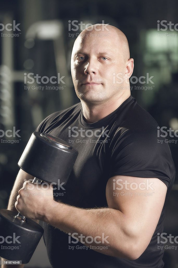 Portrait of Strong Man Lifting Dumbbell in the Gym royalty-free stock photo