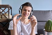istock Portrait of student boy teenager in headphones looking at webcam, videocall 1262873041