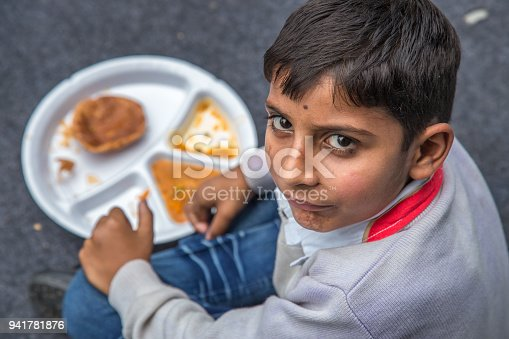 941788480 istock photo Portrait of Student having mid-day meal in Indian school. 941781876