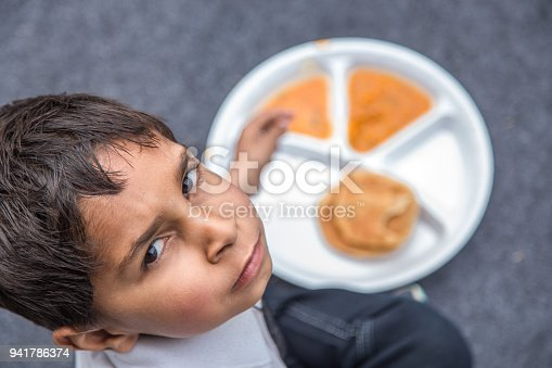 941788480 istock photo Portrait of Student having mid-day meal in Indian school. 941786374