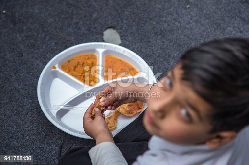 941788480 istock photo Portrait of Student having mid-day meal in Indian school. 941788436
