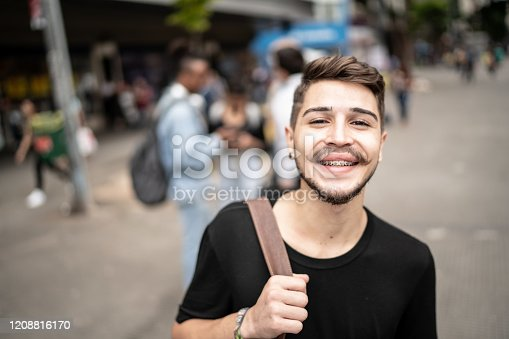 972902010 istock photo Portrait of student young man on the street 1208816170