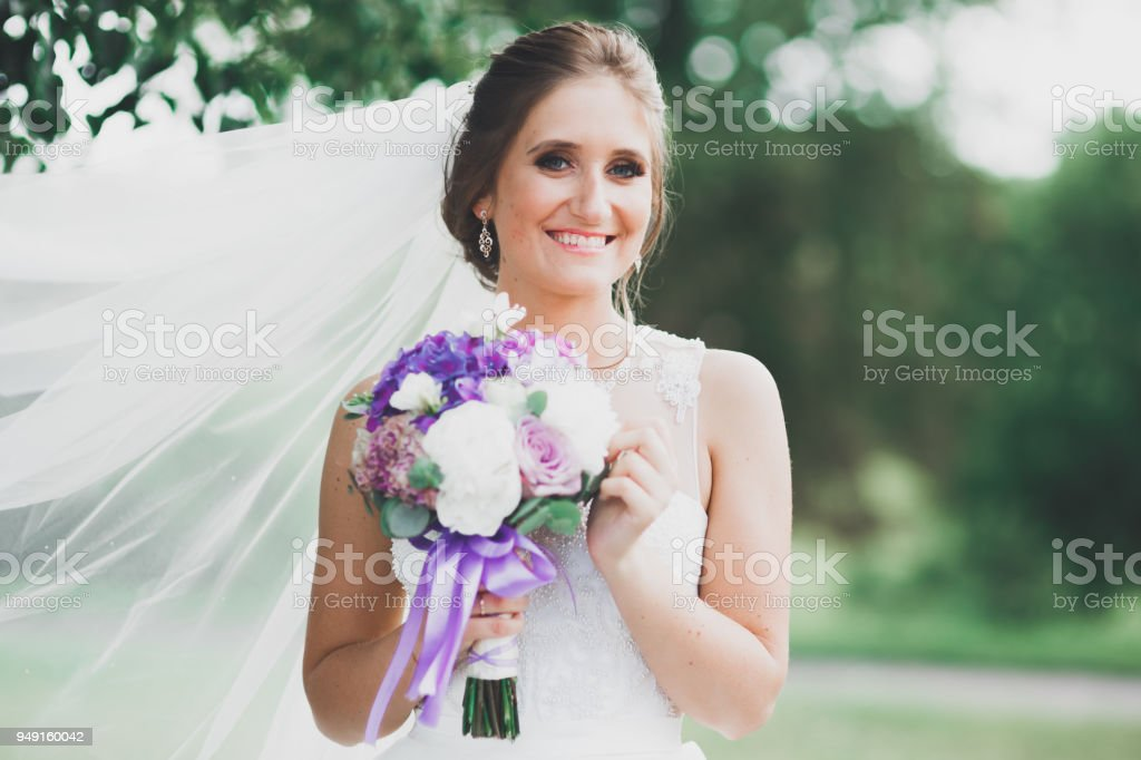 Portrait of stunning bride with long hair posing with great bouquet stock photo