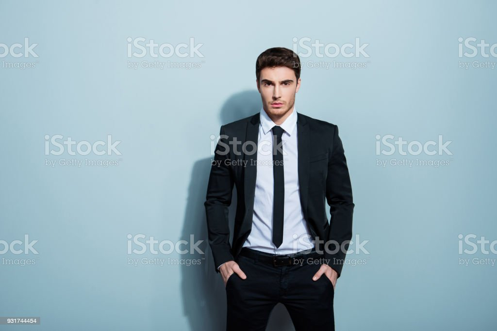 Portrait of stunning classy chic cool confident serious minded focused concentrated young boss chief holding hands in pockets looking at camera isolated on gray background copy-space stock photo