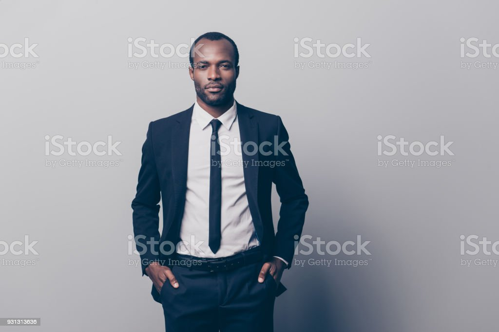 Portrait of stunning, manly, brutal man in black tux, tuxedo with white shirt and tie, holding two hands in pockets of pants, looking at camera, going for meeting, isolated on grey background stock photo