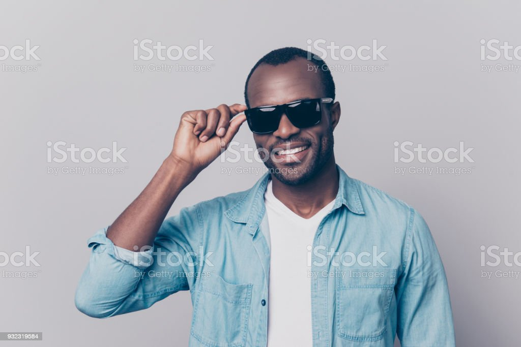 Porträt von atemberaubenden, perfekte Mann mit strahlenden Lächeln, schwarze Haut, schwarze Sommer Brille hält Öse der Brille im Gesicht, Blick in die Kamera, auf grauem Hintergrund isoliert – Foto