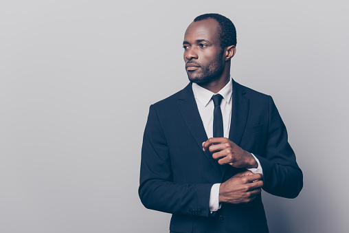 istock Portrait of stunning, trendy, attractive, dreamy, perfect man in black suit with tie fasten button on sleeve cuffs of white shirt, looking to the side, isolated on grey background 931346616