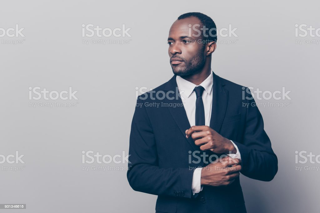 Portrait of stunning, trendy, attractive, dreamy, perfect man in black suit with tie fasten button on sleeve cuffs of white shirt, looking to the side, isolated on grey background stock photo