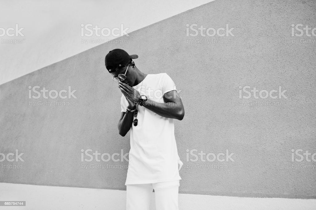 Portrait of stylish african american boy praying hands, wear on white clothes,glasses and cap against wall. Street fashion of young black people. zbiór zdjęć royalty-free