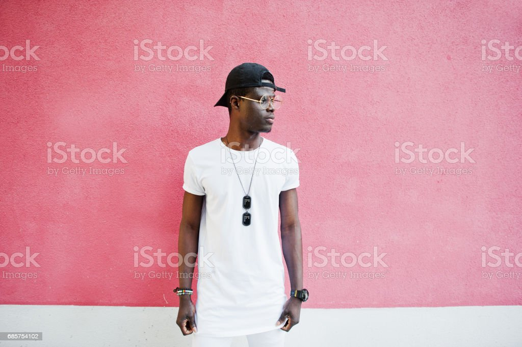 Portrait of stylish african american boy, wear on white clothes,glasses and cap against pink wall. Street fashion of young black people. royaltyfri bildbanksbilder
