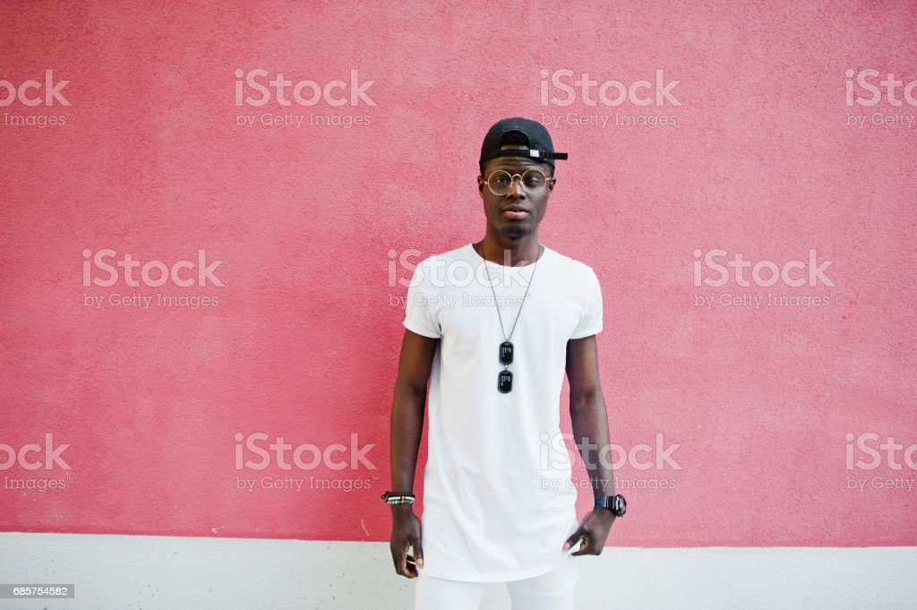 Portrait of stylish african american boy, wear on white clothes,glasses and cap against pink wall. Street fashion of young black people. zbiór zdjęć royalty-free