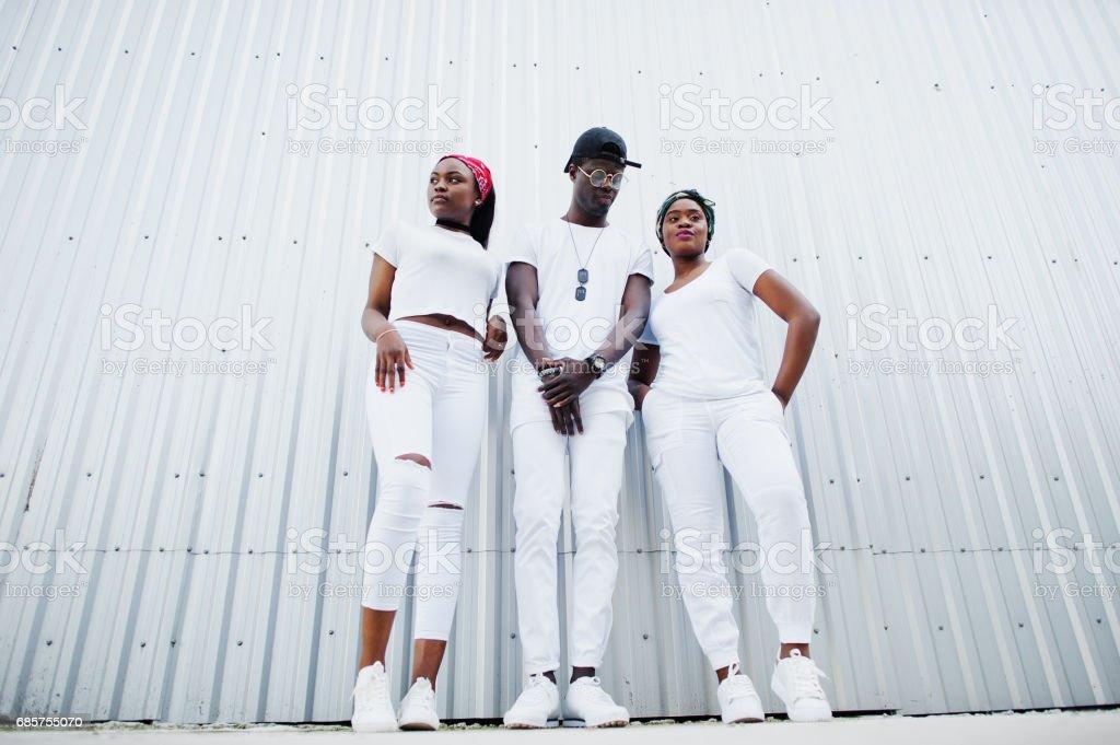 Portre iki kızla şık Afro-Amerikan çocuk çelik duvara beyaz giysiler giymek. Sokak moda siyah gençlerin. stok fotoğrafı