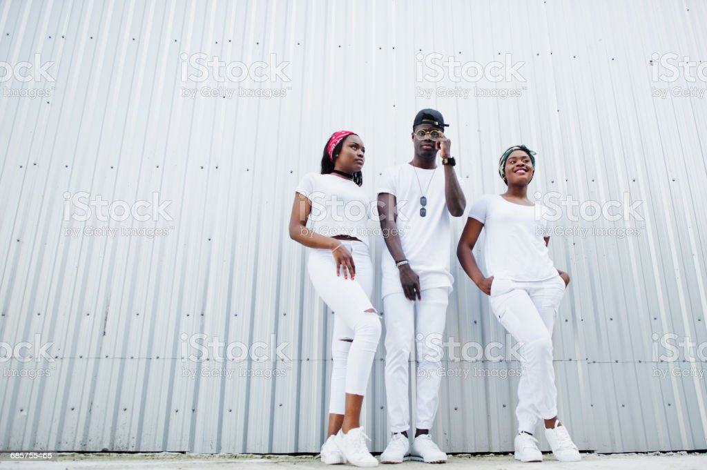Portrait of stylish african american boy with two girls, wear on white clothes, against steel wall. Street fashion of young black people. stok fotoğrafı