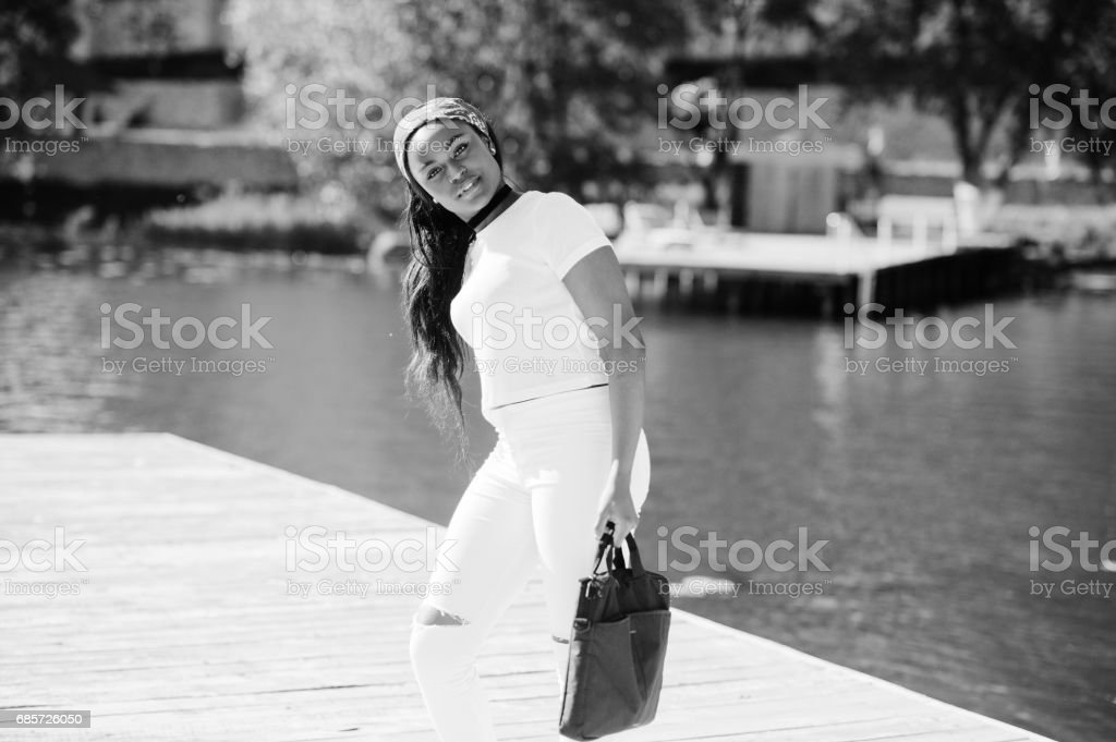Portrait of stylish african american girl, wear on white clothes, with bag on hand against pier of lake. Street fashion of young black people. royalty-free 스톡 사진