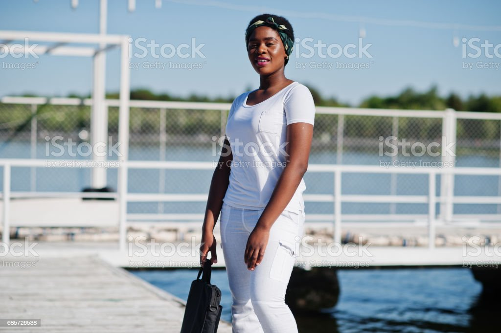 Portrait of stylish african american girl, wear on white clothes, with bag on hand against pier of lake. Street fashion of young black people. Lizenzfreies stock-foto
