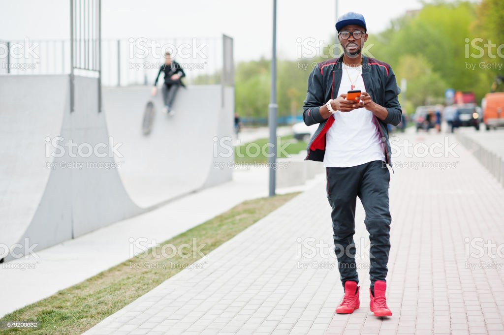 Portrait of stylish african american man on sportswear, cap and glasses looking on his phone. Black men model walk at skate park. photo libre de droits