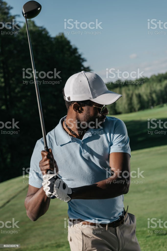 portrait of stylish african american man playing golf at golf course