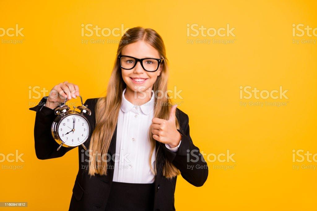 Portrait of stylish beautiful, trendy little kid hold hand clock...