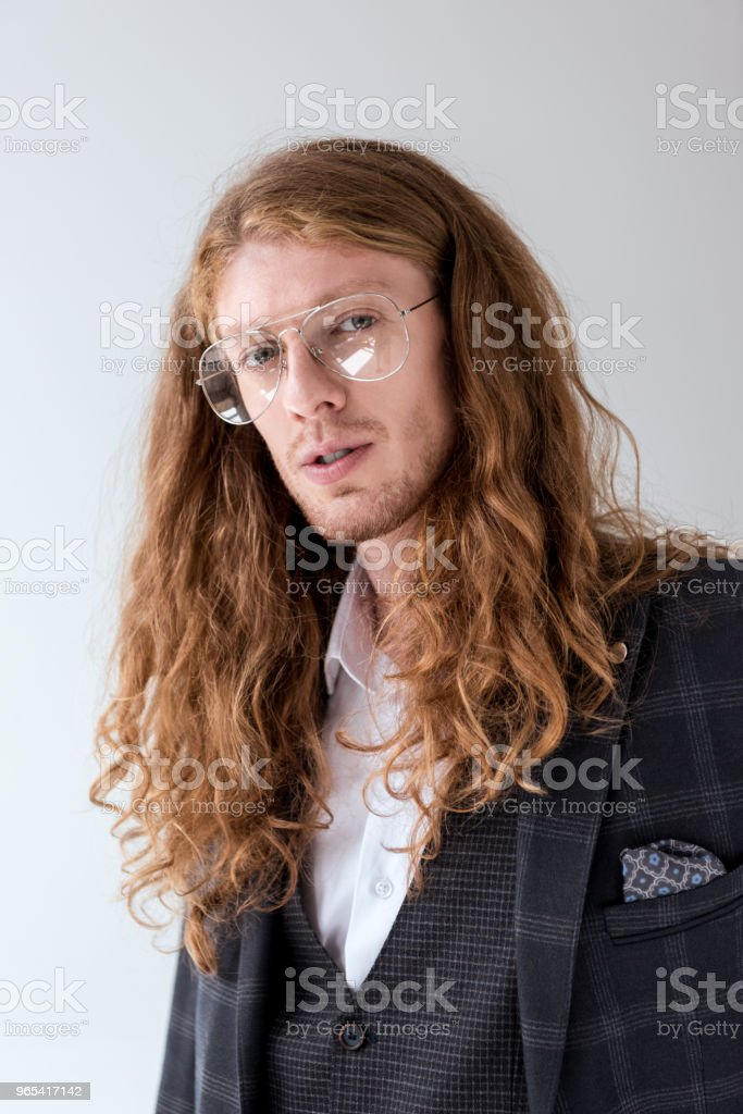 portrait of stylish businessman with curly hair looking at camera zbiór zdjęć royalty-free