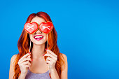 istock Portrait of stylish cheerful funny happy carefree girl with ginger hair hide her eyes behind sweet gingerbread with red heart form with stick while standing on blue background 941889534