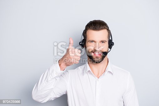 istock Portrait  of stylish, cheerful, harsh, virile, attractive operator having headset with microphone on head showing thumb up with finger looking at camera isolated on grey background 970425566